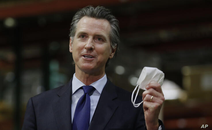 Gov. Gavin Newsom displays a face mask as he urges people to wear them to fight the spread of the coronavirus during a news…