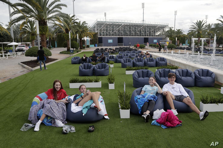People sit outdoors watching a movie as part of the Outdoor Theater program offered by the Miami Dolphins at Hard Rock Stadium…