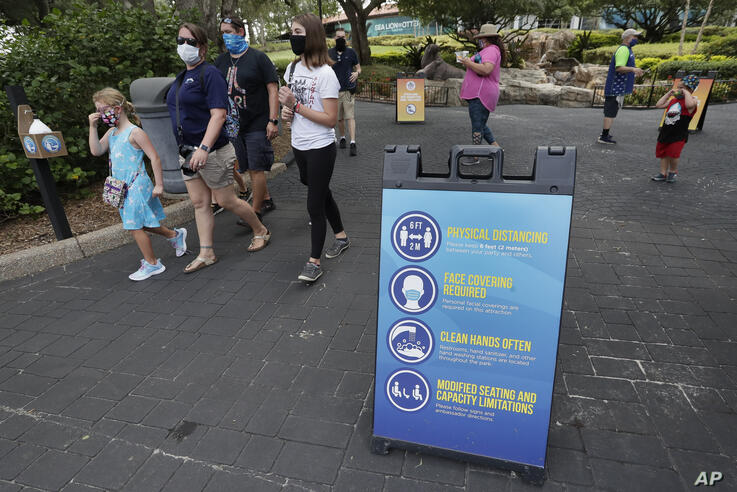 Signs remind guests of new safety measures in place at SeaWorld as it reopened, Thursday, June 11, 2020, in Orlando, Fla. The…