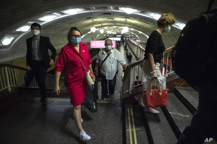 People wearing face masks to protect against coronavirus walk through the subway in Moscow, Russia, Wednesday, June 10, 2020…
