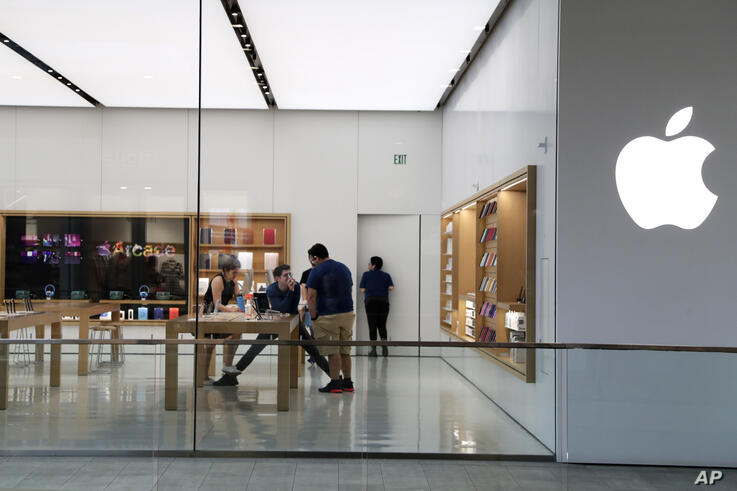 FILE - In this March 14 2020 file photo, Apple employees work inside a closed Apple store in Miami. Apple is temporarily…