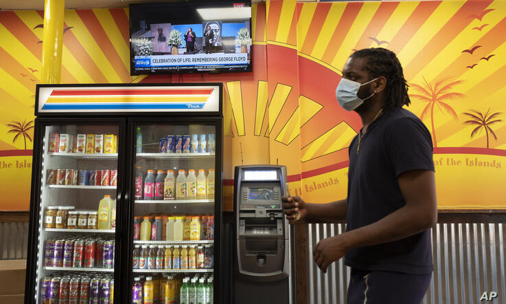 A customer waits in line at Golden Krust Caribbean restaurant, Tuesday, June 9, 2020, in Mount Vernon, N.Y. while the memorial…