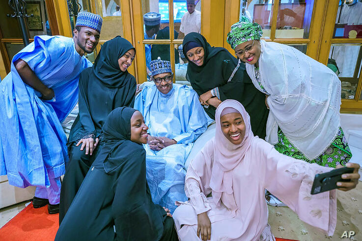 In this photo released by the Nigeria State House Nigeria's President Muhammadu Buhari, centre, takes a selfie with family…