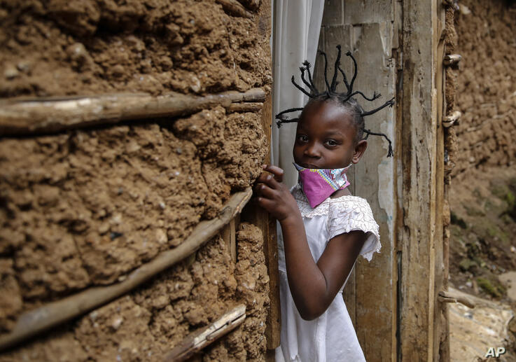 FILE - In this Sunday, May 3, 2020 file photo, Jane Mbone, 7, arrives home after having her hair styled in the shape of the new…