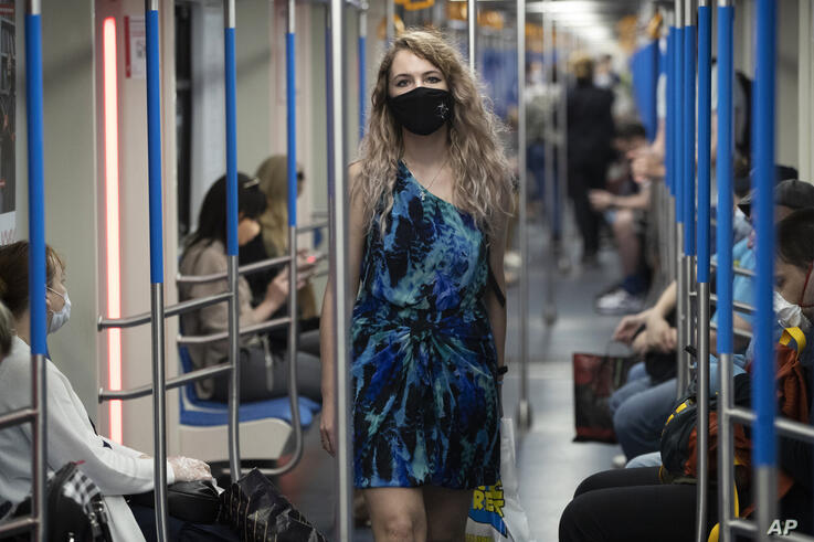 A woman wearing a face mask to protect against coronavirus walks in a carriage of a subway in Moscow, Russia, Wednesday, June…