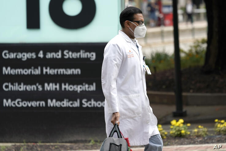 A healthcare professional walks through the Texas Medical Center Thursday, June 25, 2020, in Houston. The leaders of several…