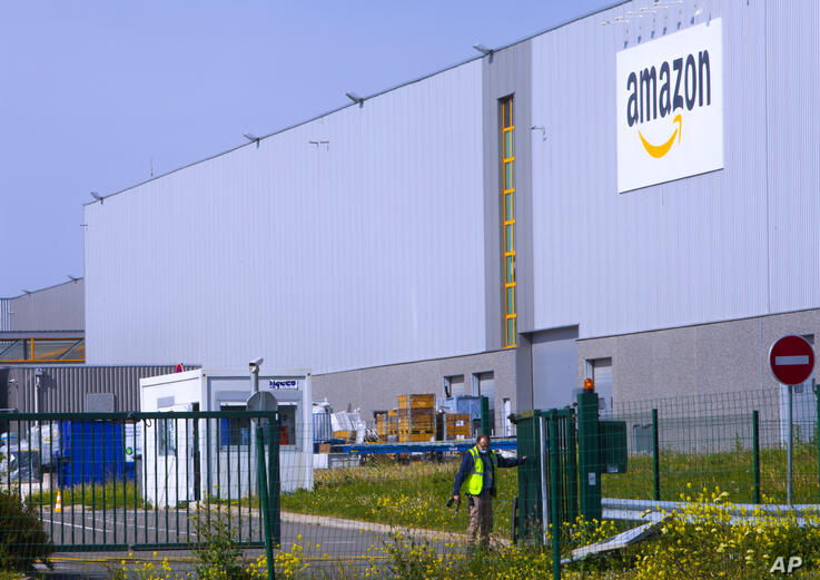 An employee closes a gate at the entrance of Amazon, in Douai, northern France, Thursday April 16, 2020. Amazon has decided to…