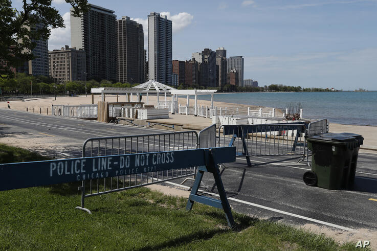 Where thousands would usually gather or pass by, a food and beverage pavilion sits unoccupied at the Oak Street beach in…