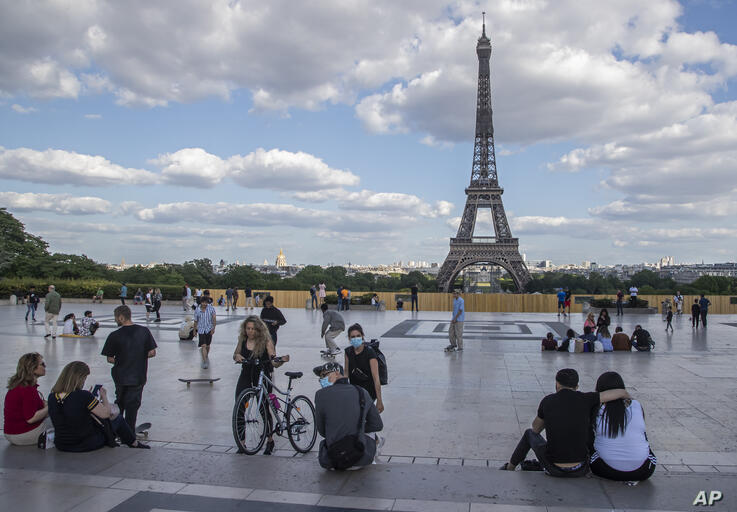 People stroll at Trocadero square near the Eiffel Tower in Paris, Monday, May 25, 2020, as France gradually lifts its Covid-19…