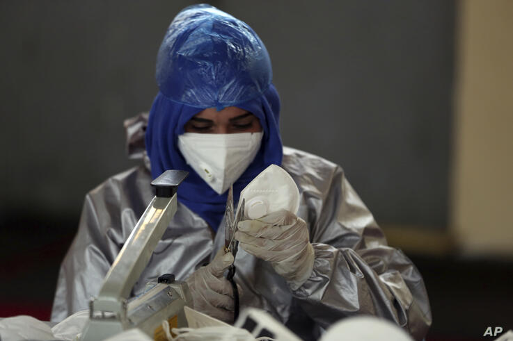 A worker trims a protective face mask to be used to curb the spread of the coronavirus at a factory in Kabul, Afghanistan,…
