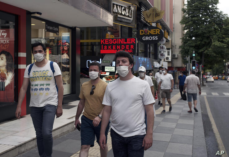 People wearing face masks to protect against the spread of coronavirus, walk in city the centre, in Ankara, Turkey, Sunday,…