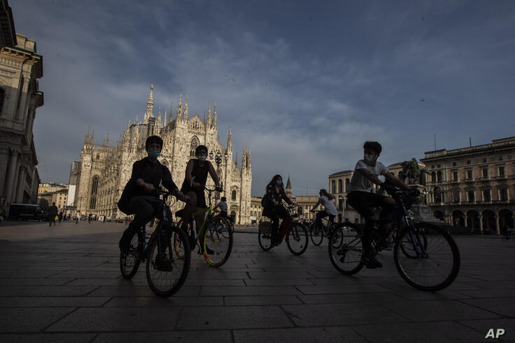 People bike in front of the Duomo gothic cathedral in Milan, Italy, Monday, May 18, 2020. . On Monday, Italians enjoyed a first…