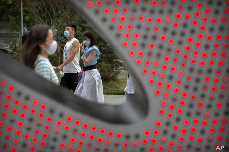 People wearing face masks to protect against the spread of the new coronavirus walk through a shopping and office complex in…
