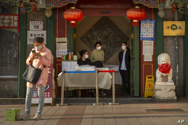 Clerks wear face masks to prevent the spread of the new coronavirus as they wait for customers at the entrance to a restaurant…