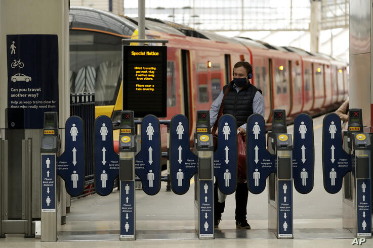 Signs requesting people keep their distance from each other are displayed on ticket barriers to help stop the spread of…