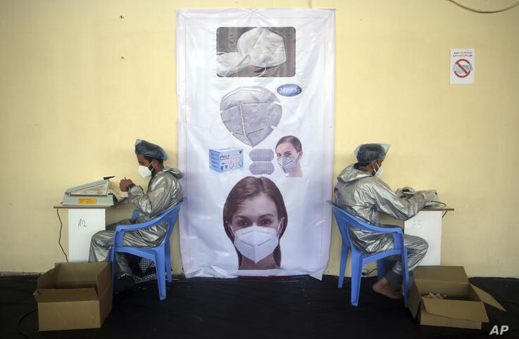 Workers make protective face masks used to curb the spread of the coronavirus at a factory in Kabul, Afghanistan, Wednesday,…