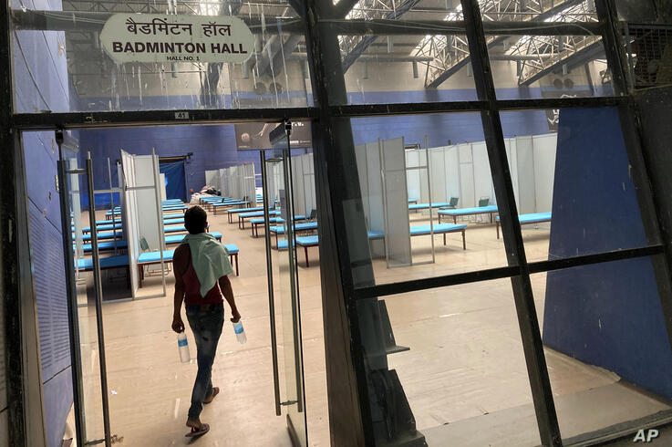A worker walks inside a makeshift COVID-19 care center at an indoor sports stadium in New Delhi, India, Tuesday, June 30, 2020…