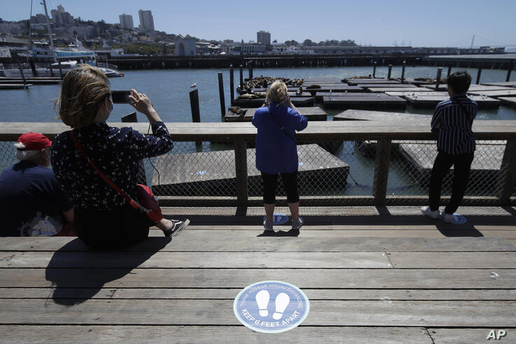 FILE - In this June 18, 2020, file photo, a sign advising visitors to maintain social distance is shown as people watch the sea…