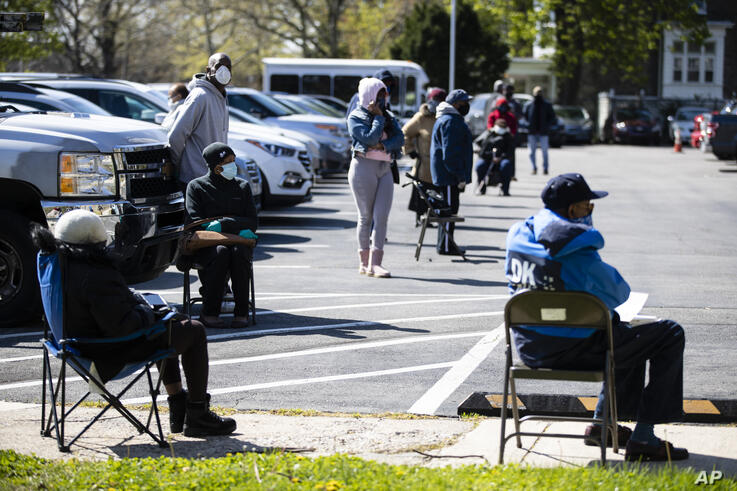 People in vehicles and those who arrived on foot wait to receive a COVID-19 test at a barrier free location outside the Pinn…