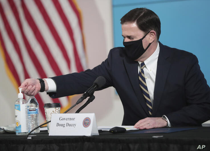 Arizona Gov. Doug Ducey uses hand sanitizer before updating reporters on COVID-19 in the state, Monday, June 29, 2020, in…