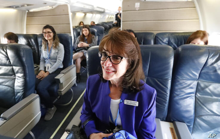 Gloria Orlandi-Kass, foreground, Miami-Dade County program director for the Alzheimer's Association, takes her seat on a Boeing…