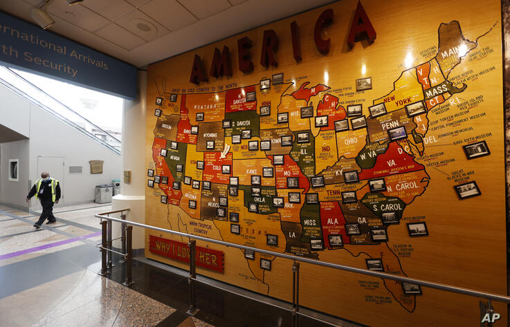 A lone security officer walks past a map of America in the main terminal of Denver International Airport as it gets back to…
