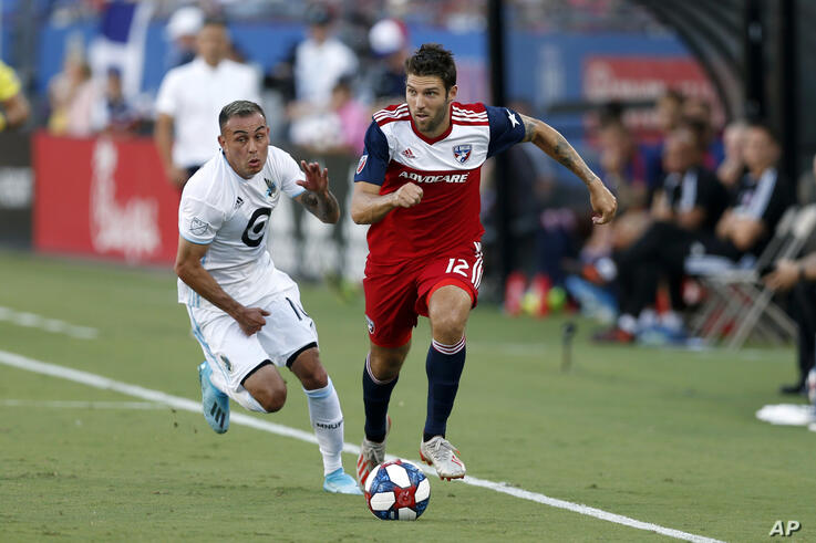 FILE - In this Aug. 10, 2019, file photo, FC Dallas defender Ryan Hollingshead plays the ball while Minnesota United forward…