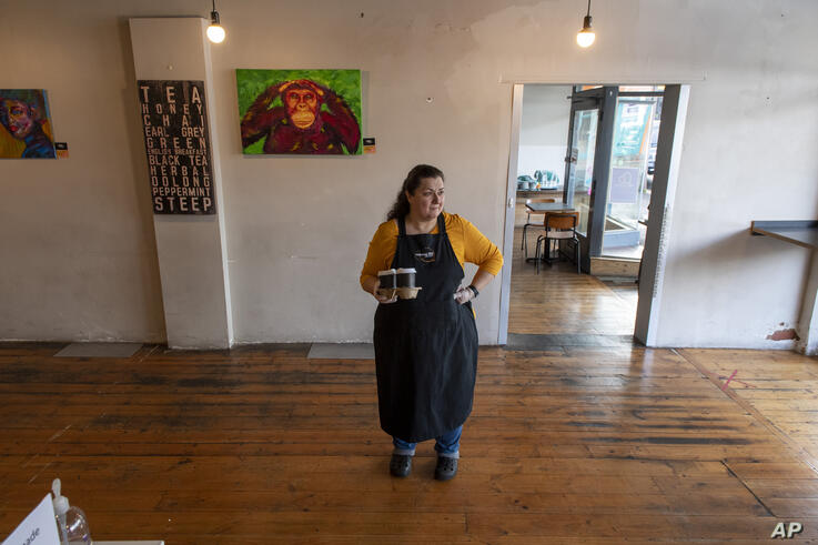 Cafe owner Maria Iatrou stands at her empty coffee shop in Melbourne, Monday, July ۶, ۲۰۲۰. As Australia is emerging from…