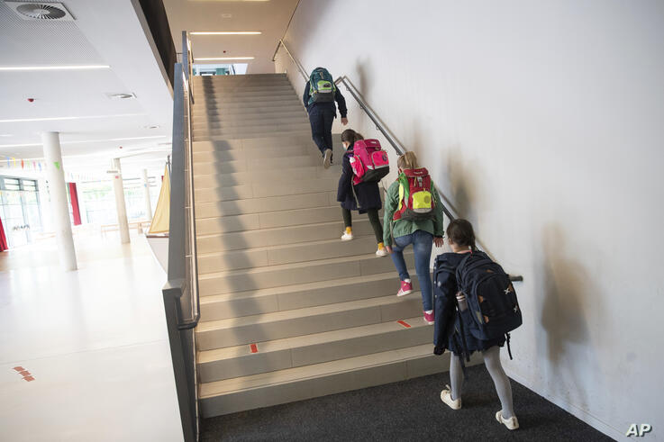 Students of a 4th grade walk at a distance on stairs to their classrooms in the Goldbeck Schoo in Hamburg, Germany, Monday, May…