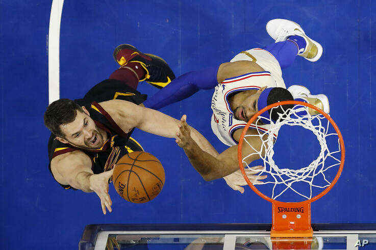 FILE - In this Dec. 7, 2019, file photo, Cleveland Cavaliers' Kevin Love, left, goes up to shoot against Philadelphia 76ers'…
