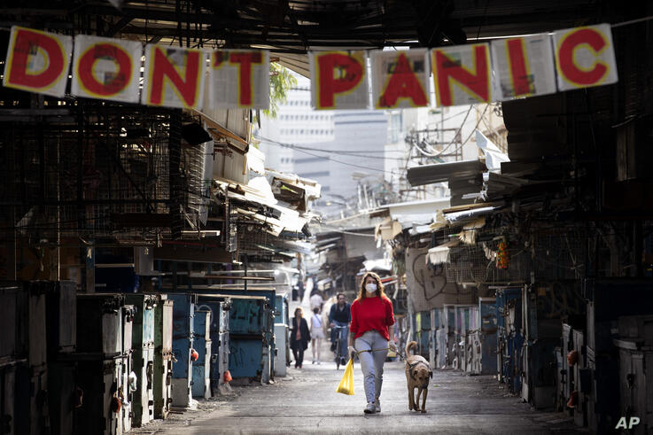 "A woman walks her dog under a ""don't panic"" sign hanging on the entrance of a food market that was shut down in order to reduce…"