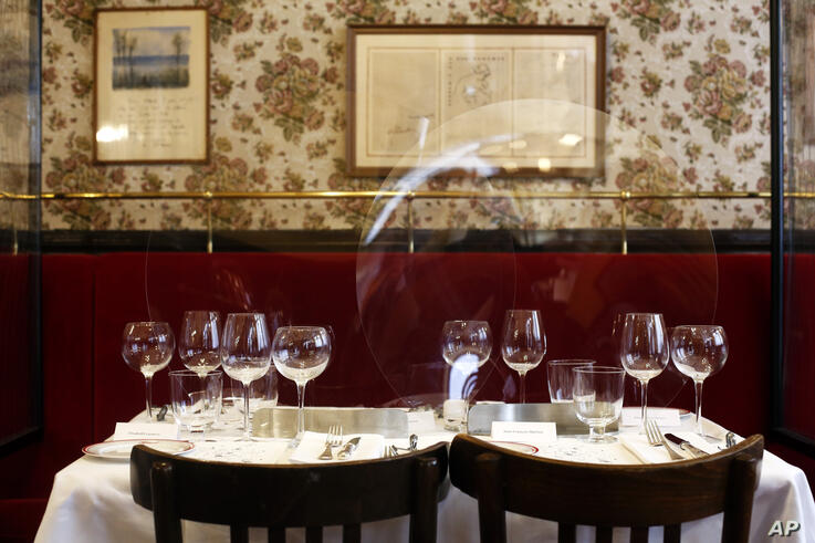Plastic shields are placed on the table of the Alain Ducasse's restaurant «Allard», in Paris, Thursday, June 11, 2020. French…