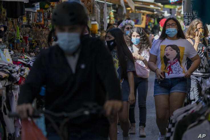 People wearing masks visit a food market that was shut down in order to reduce the spread of the coronavirus, as markets,…