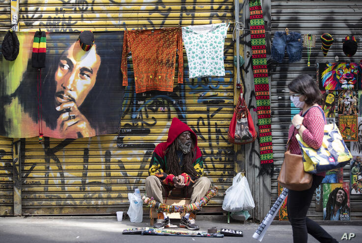 A street vendor sells his merchandise in front of shuttered stores on a sidewalk left empty due to a quarantine imposed by the…