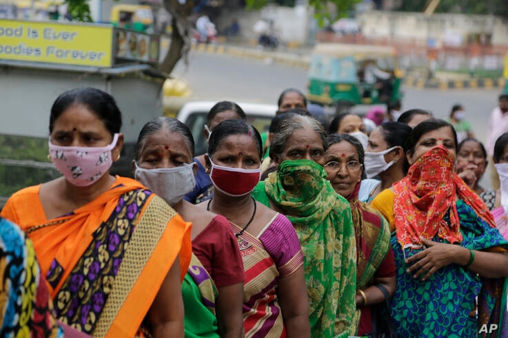 Indian women wear face masks as a precaution against coronavirus stand in queue to submit their form to update their details to…