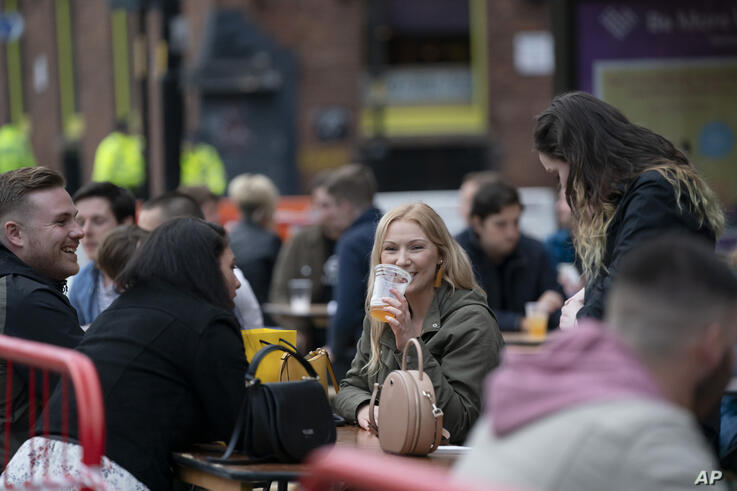 Members of the public are seen at a bar in Manchester's Northern Quarter, England, Saturday July 4, 2020. England is embarking…