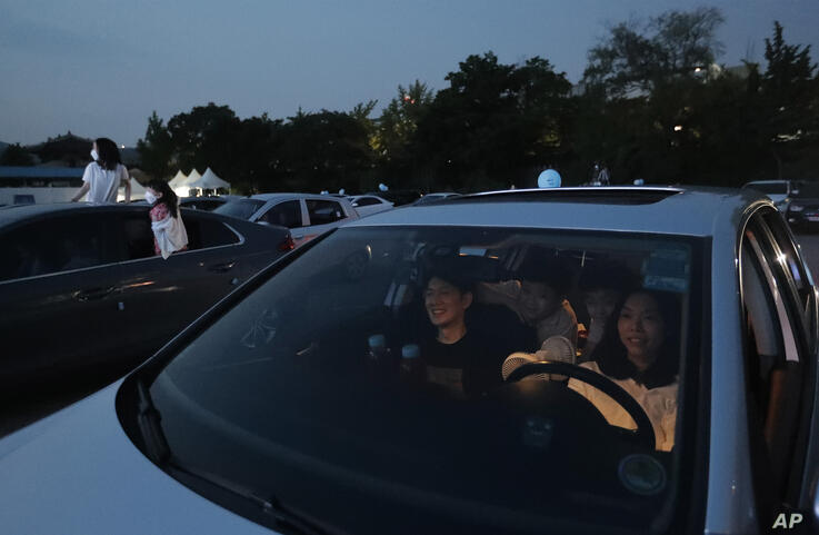 Family members in a car watches a drive-in concert at Gyeongbok Palace parking lot in Seoul, South Korea, Friday, July 17, 2020…