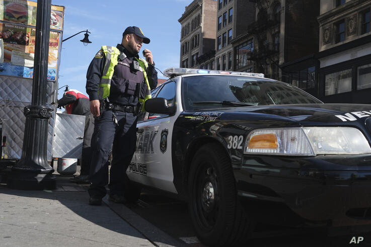 A Newark police officer uses his car megaphone to encourage social distancing at an intersection in Newark, N.J., Thursday,…