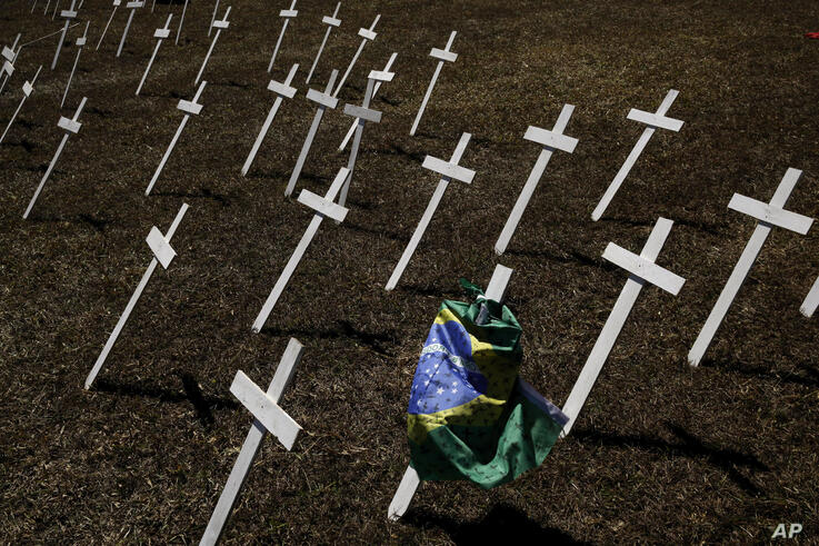Rows of crosses representing the thousands of deaths due to the new coronavirus are displayed on a lawn during a protest…