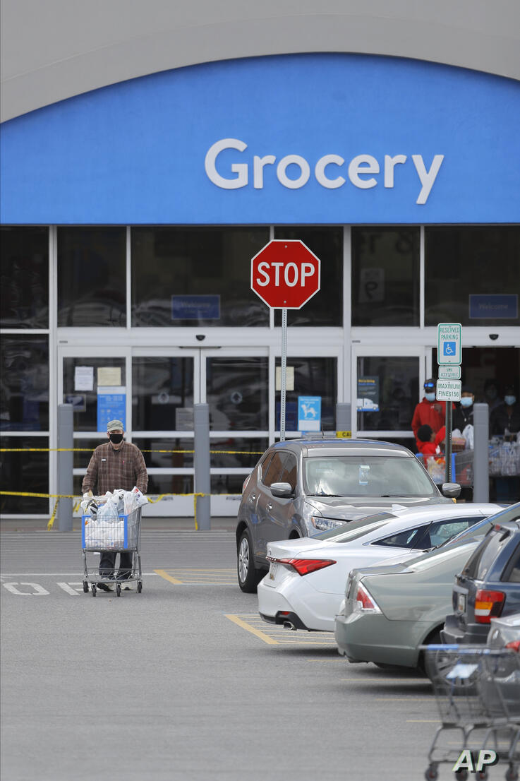 A man pushes a shopping cart after exiting a Walmart store, Tuesday, May 12, 2020, in Cockeysville, Md. (AP Photo/Julio Cortez)