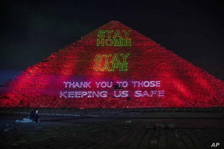 A journalist looks at his mobile phone as the Ministry of Antiquities lights up the pyramids in an expression of support for…