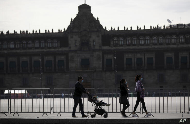 Pedestrians wearing face masks amid the COVID-19 pandemic walk past the National Palace, the president's office, in an empty…