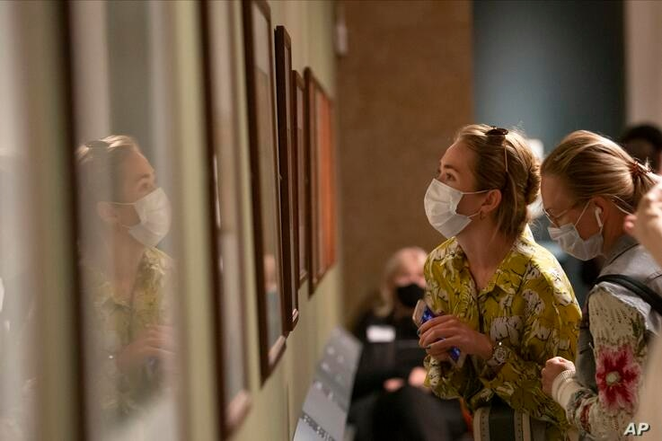 """Visitors wearing face masks to protect against coronavirus, look at the exhibition """"From Durer to Matisse Selected drawings""""…"""