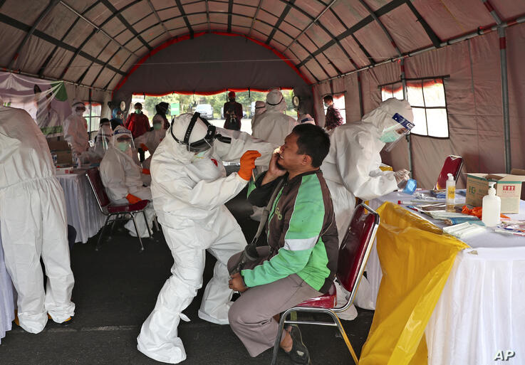 A man reacts as a health worker collects his nasal swab samples during a mass test for the new coronavirus in Tangerang,…