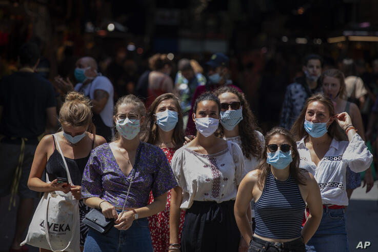 Tourists wearing face masks wait to cross a road in downtown Barcelona, Spain, Thursday, July 16, 2020. With Europe's summer…
