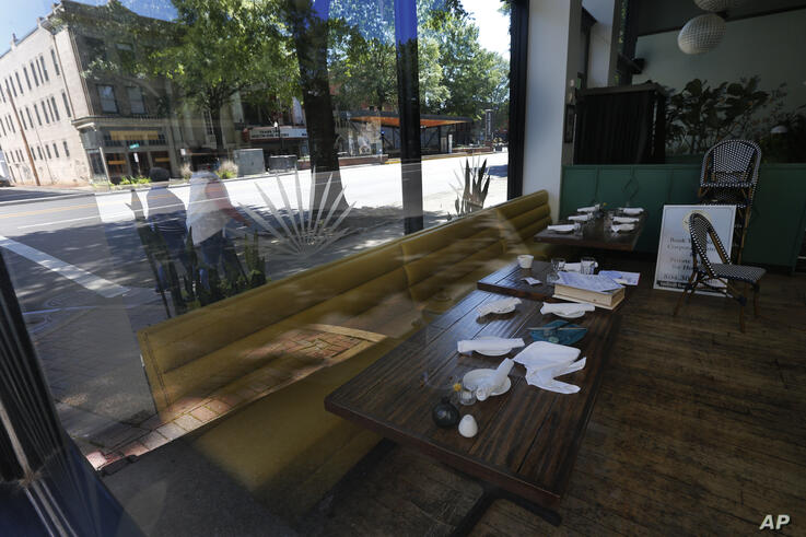 Tables are set but no customers at Bar Solita a closed restaurant Thursday May 7, 2020, in Richmond, Va. The restaurant group…
