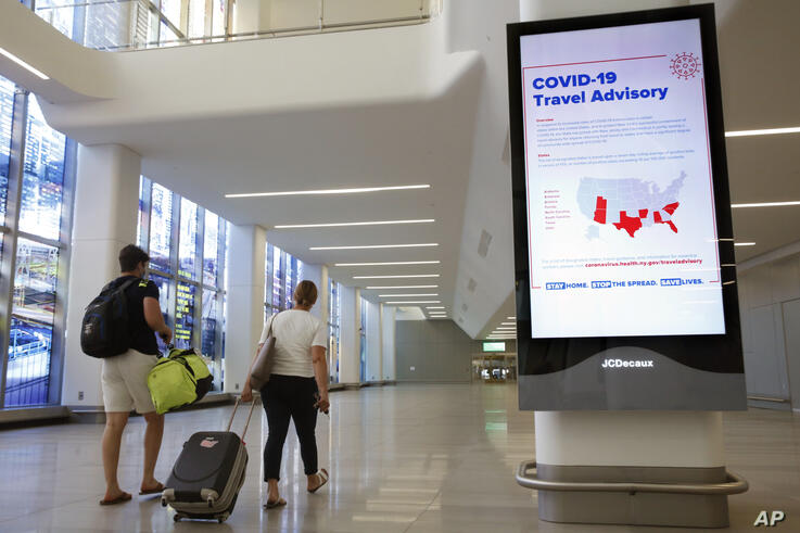 FILE - In this June 25, 2020, file photo, arriving travelers walk by a COVID-19 travel advisory sign in the baggage claim area…