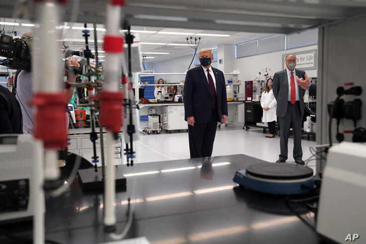 President Donald Trump wears a face mask as he participates in a tour of Bioprocess Innovation Center at Fujifilm Diosynth…