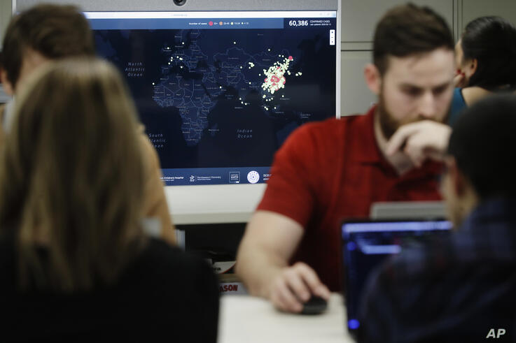 In this Thursday, Feb. 13, 2020 photo, Kyle Martin, a worker at HealthMap, a system using artificial intelligence to monitor…