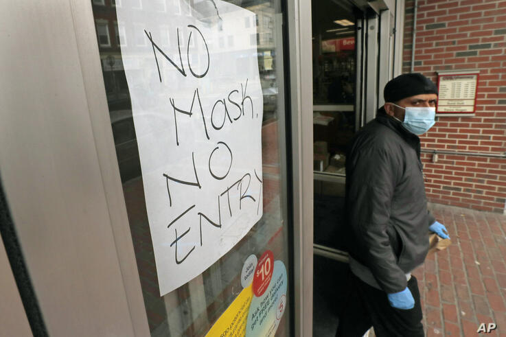 A masked shopper walks past a sign taped to the front door of a CVS Pharmacy, requesting patrons wear masks if they intend on…